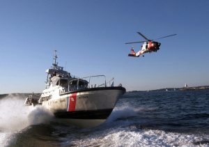 BOSTON - Two Massachusetts based Coast Guard assets, a 47-foot motor lifeboat from Station Gloucester and a Jayhawk helicopter from Air Station Cape Cod, transit out of the Gloucester Harbor during a training exercise Aug. 25. Coast Guard photo by Luke Pinneo